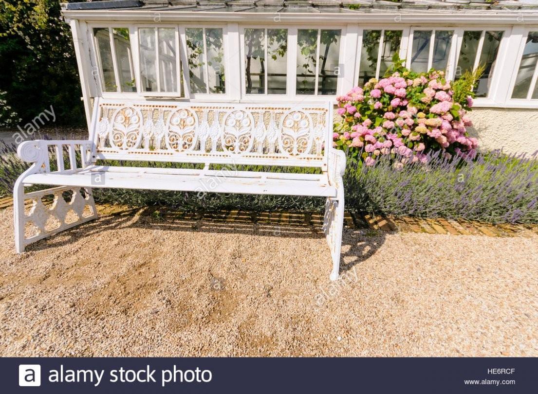 Weißes Gusseisen Gartenbank Neben Einem Gewächshaus Stockfoto Bild von Gartenbank Gusseisen Weiß Bild