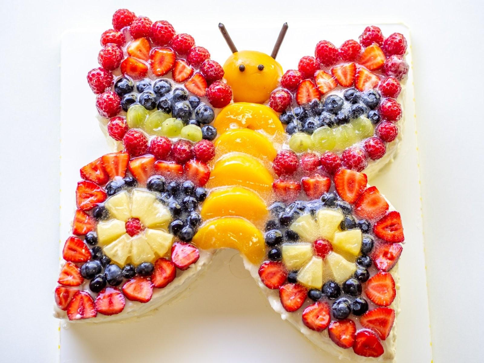 Bunter Schmetterlingstorte Mit Viel Obst Dekoriert  Perfekt Für Kinder von Obst Deko Für Kindergeburtstag Bild