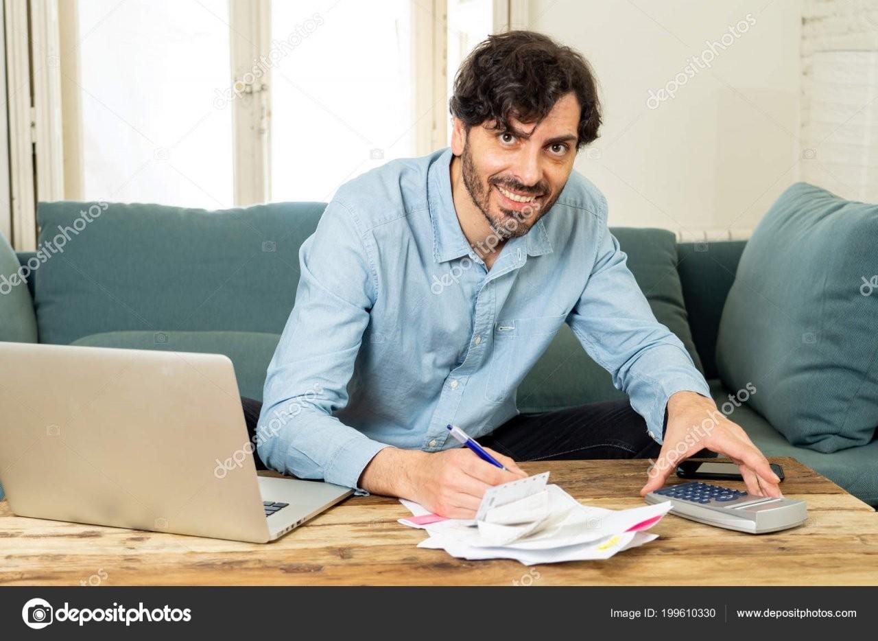 Glücklich Attraktive Latin Mann Berechnung Persönliche Finanzen von Buchhaltung Von Zu Hause Photo