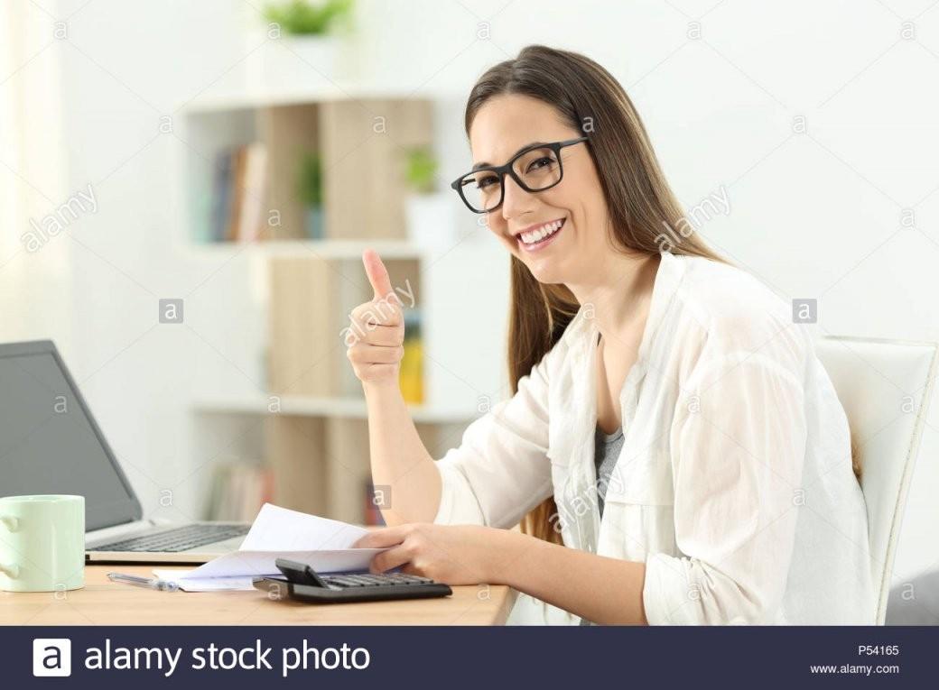 Glückliche Dame Buchhaltung Und Gestikulierend Daumen Bis Zu Hause von Buchhaltung Von Zu Hause Bild